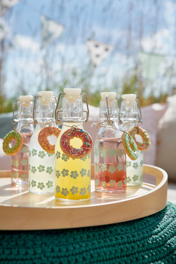 Patterned KORKEN bottles with stoppers filled with colourful drinks.