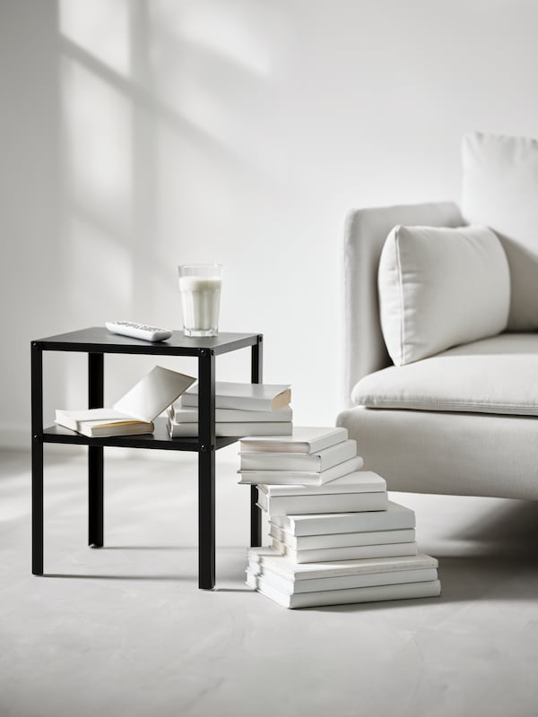 A black KNARREVIK side table by a white sofa with a glass of milk on top and a pile of white books on the floor beside it.