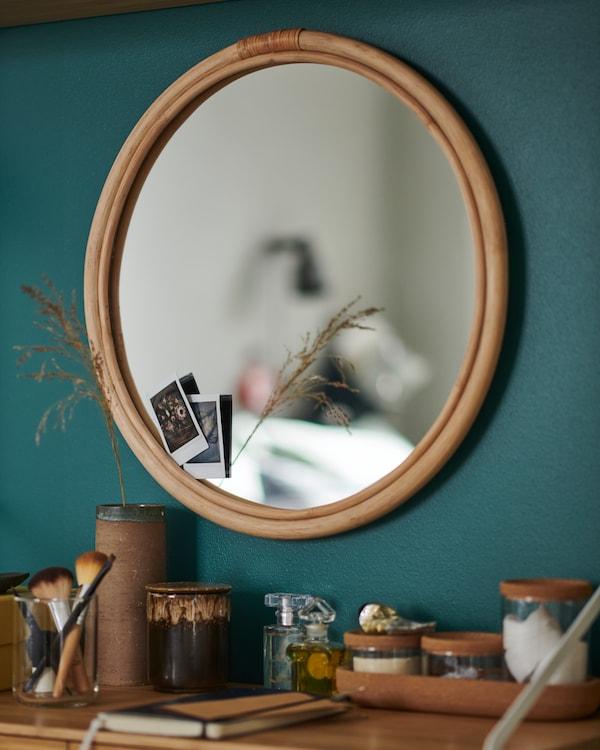 Un petit miroir rond en rotin accroché à un mur vert au-dessus d'une commode chargée.