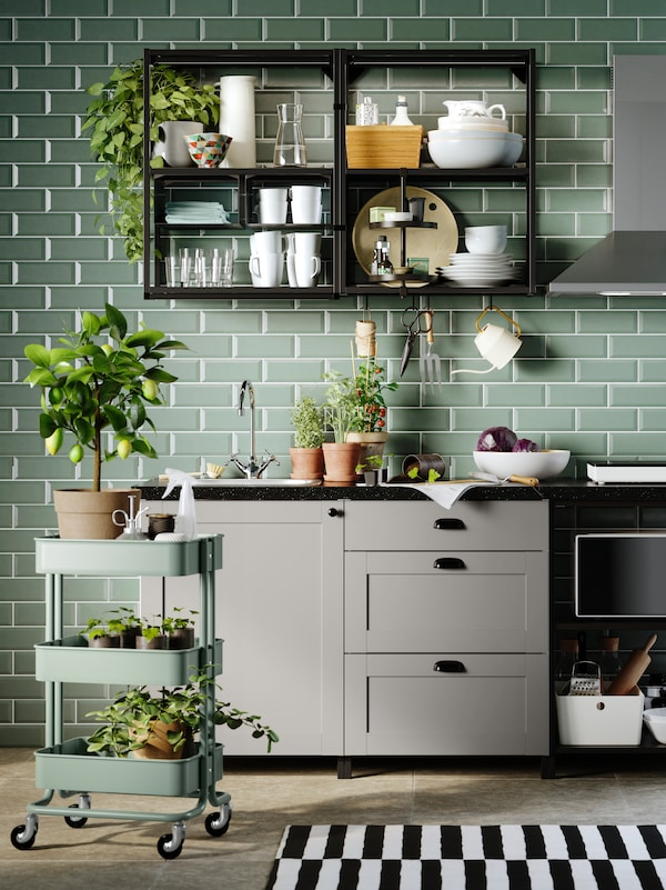 Et ENHET køkken med grå fronter og stel i antracit/grå imod en væg med grønne fliser samt et rullebord med planter.