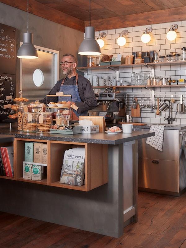 Muž stojí za pultom kaviarne, na podnosoch je čerstvé pečivo a koláčiky, zo stropu visia sivé závesné lampy, na pulte je biela šálka na kávu a v pozadí nástenné police.