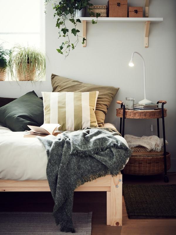 Au bord d'un lit, un coin lecture agrémenté de coussins verts et de plaids, de plantes, et d'une table roulante avec rangement accueillant une liseuse et des livres.