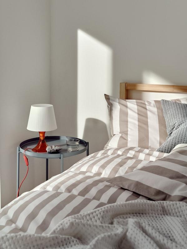 Une chambre à coucher décorée avec une housse de couette BÄRALM, une table basse GLADOM avec un plateau et une lampe de table LAMPAN