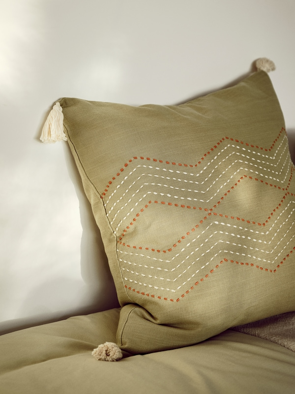 Details of handmade stitching and cream decorative tassels on the green HALLVI cushion cover.