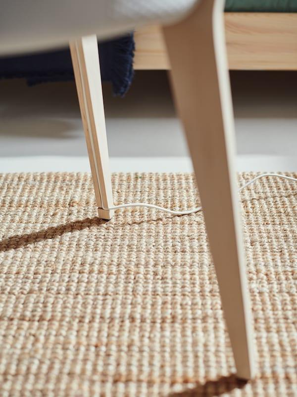 Kábel egy vájatba rejtve egy STARKVIND asztal lábában, légtisztítóval.