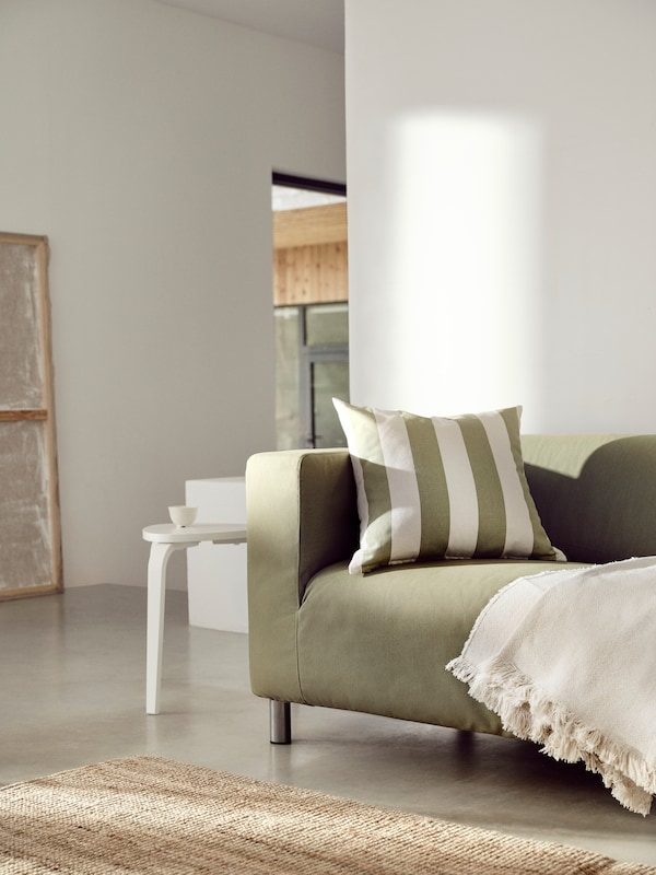 A cushion in a green natural/striped HILDAMARIA cushion cover and a throw lie on a yellow-green KLIPPAN sofa.