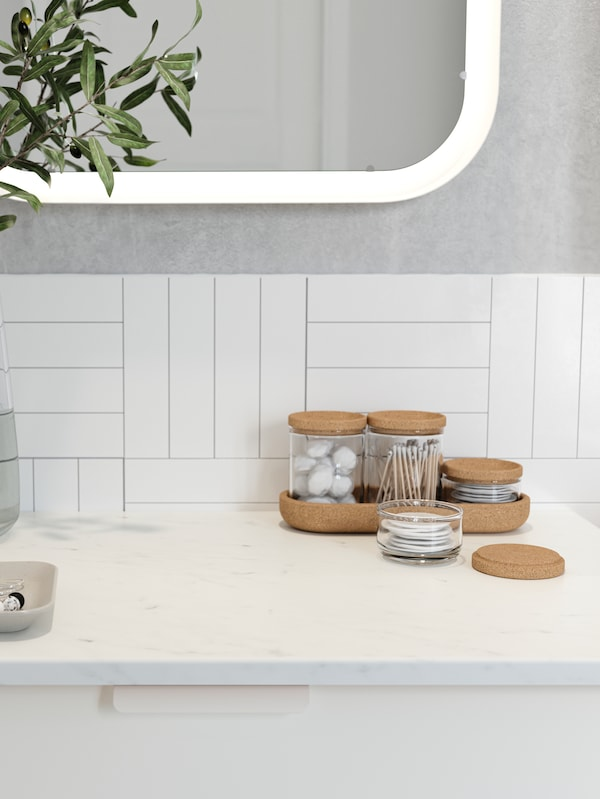 Kapas kesat dan bebola wul kapas di dalam balang kaca dengan penutup gabus pada sink cuci tangan dengan kesan marmar berwarna putih.