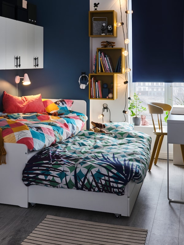 A SLÄKT bed stands in a child's bedroom with its underbed pulled out. Both are covered in colourful GRACIÖS bed linen.
