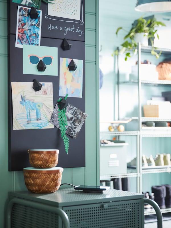 Twee zwarte magneetborden tegen een groene muur gevuld met kaartjes en aandenken.
