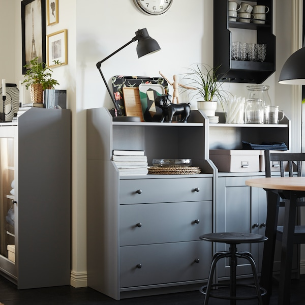 HAUGA grey sideboard sitting in dining room with books and decor stacked