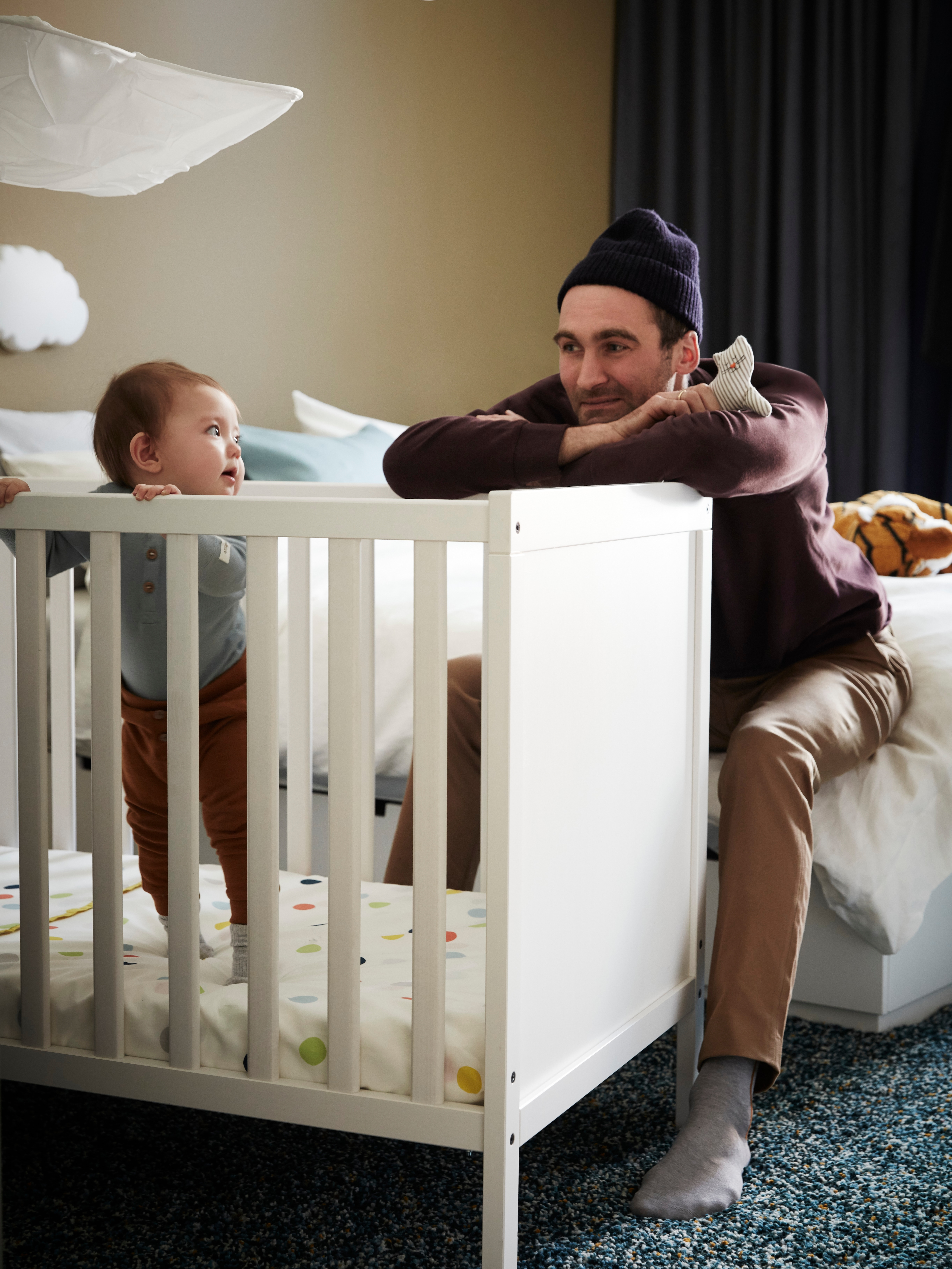 A man holding a soft toy looking at a child who is standing up in a SUNDVIK white cot.