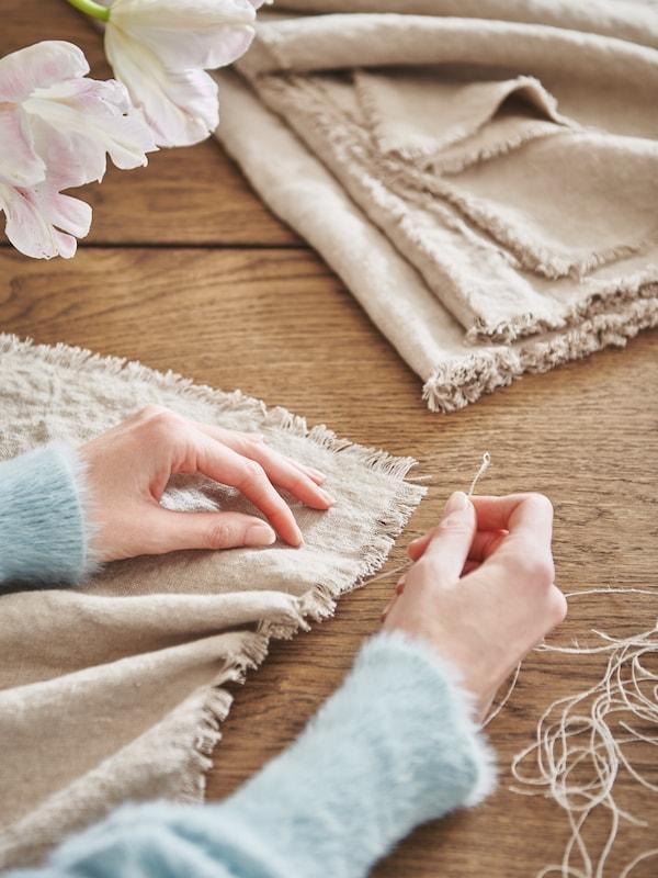يدان تقومانبشكلفني بتنسيلأطراف قماشAINAبالمتر من خلالشد الخيوط من الحواف.