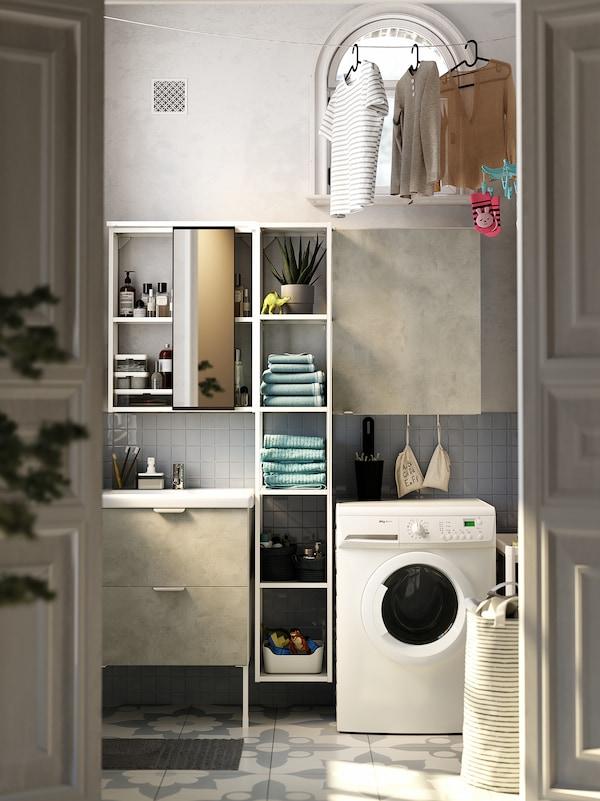 Vitt och grått tvättställ, vita öppna och stängda ENHET hyllor, tvättmaskin och tröjor som torkar på en tvättlina.