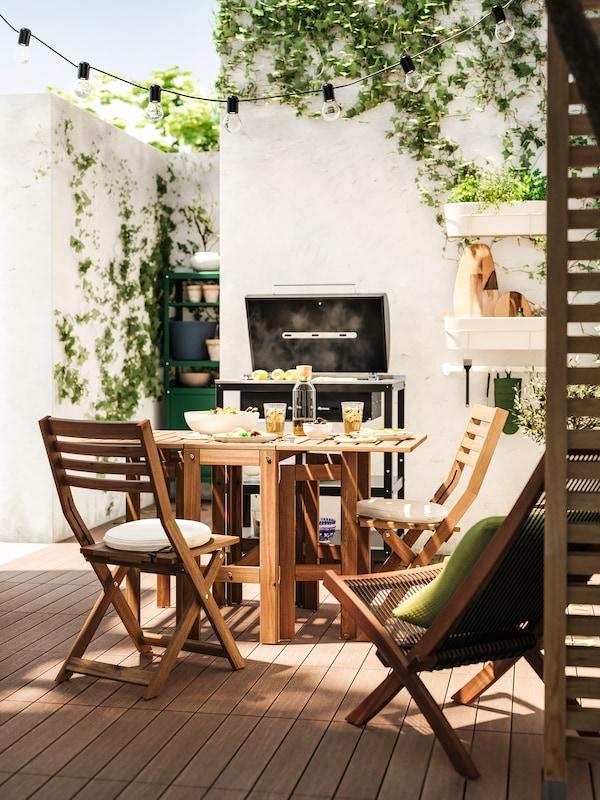 ÄPPLARÖ 에플라뢰 브라운스테인 테이블과 두 개의 접이식 의자가 놓여 있고 화이트 돌벽으로 둘러싸인 밝은 야외 공간.