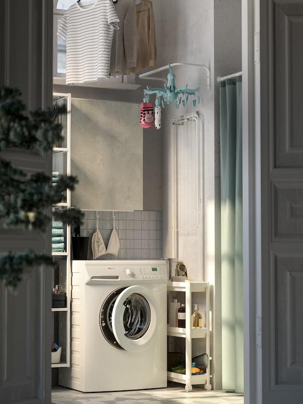 Tvätthörna med tvättmaskin, grått skåp med dörr, vit smal rullvagn, klädstång som sitter på väggen.