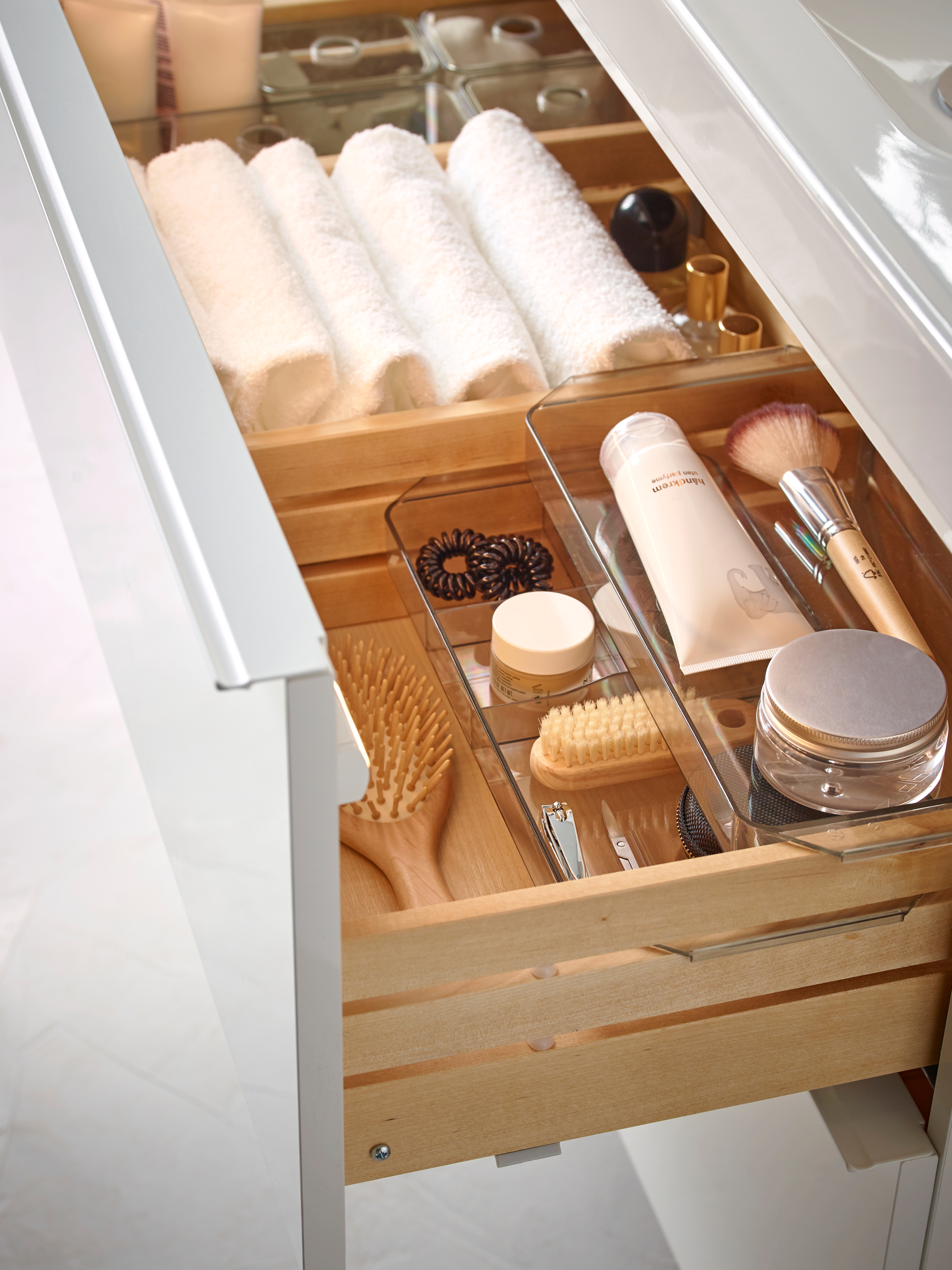 Open drawer with VÅGSJÖN bath towels, two GODMORGON storage units stacked on one another, and makeup tools and cosmetics.
