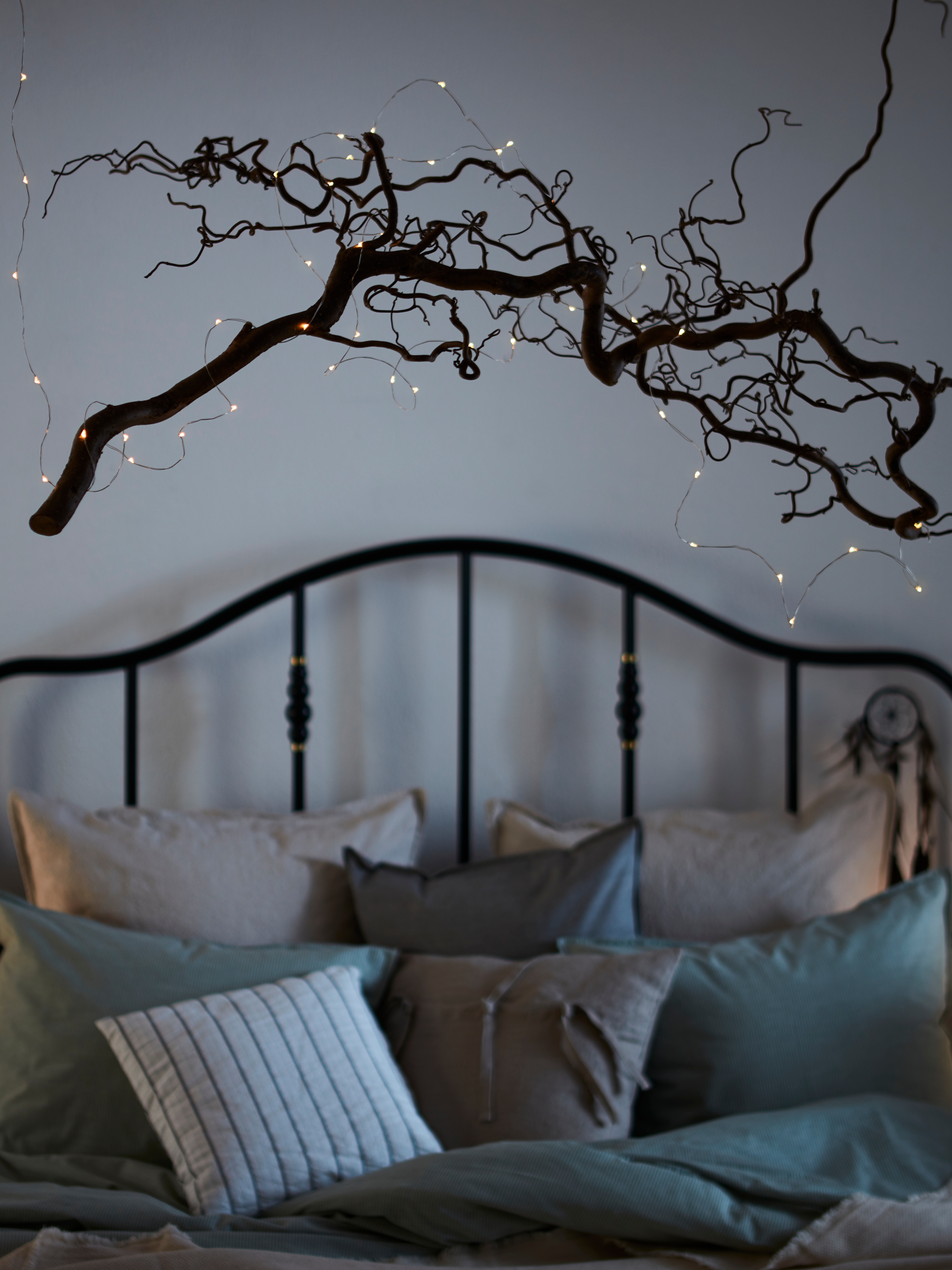 VISSVASS LED lighting chain is wrapped around a gnarled branch suspended over a wrought-iron bed that's covered with pillows.