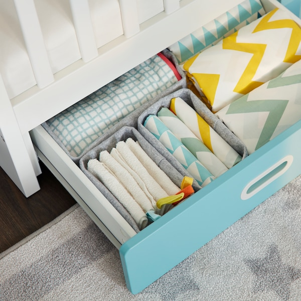 Part of a STUVA/FRITIDS crib with drawers where a drawer is open and holds different colored STILLSAMT bed linen.