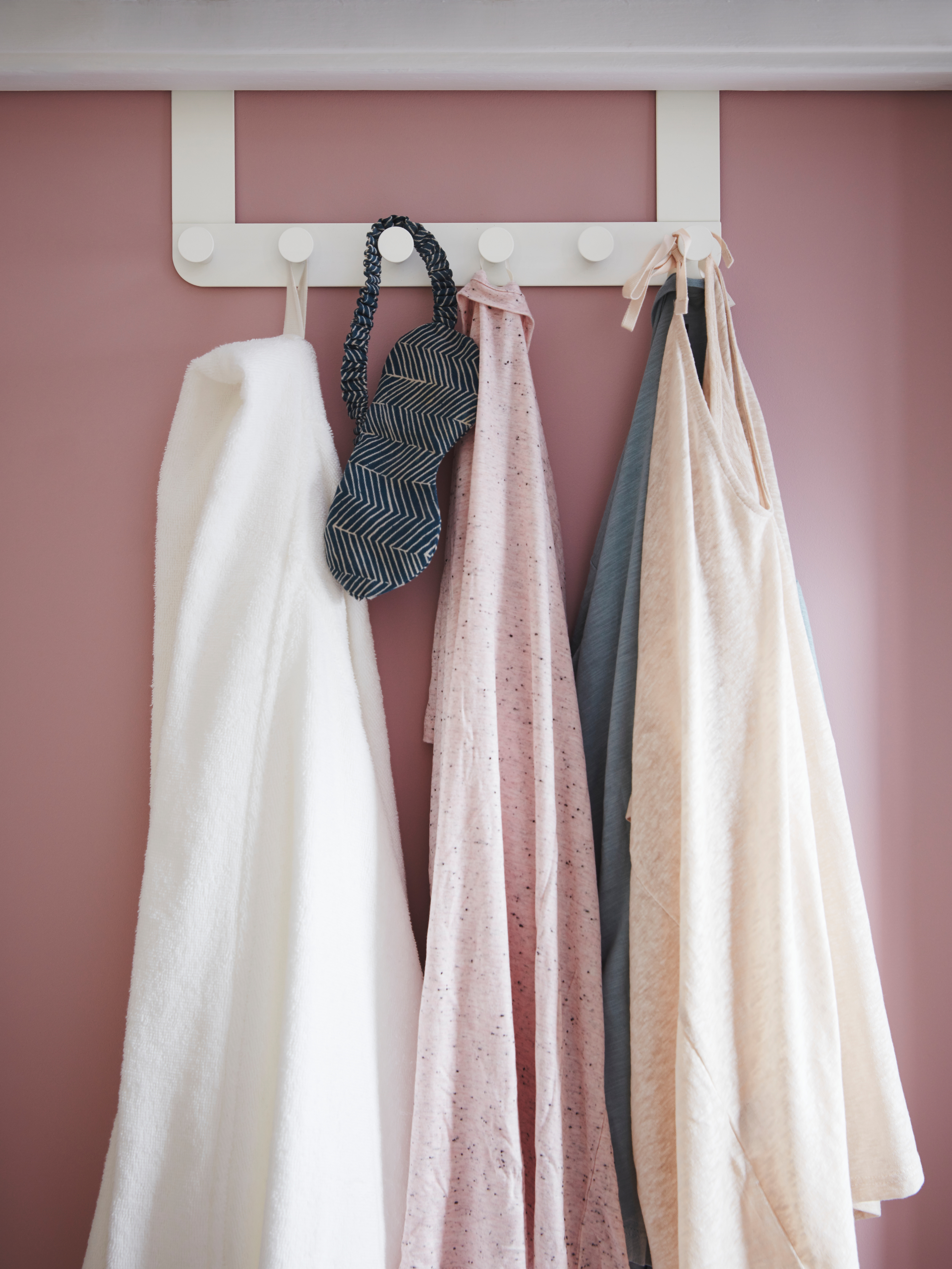 Pink door with white steel door hanger with plastic knobs with white robe, clothes and sleep mask attached to it.