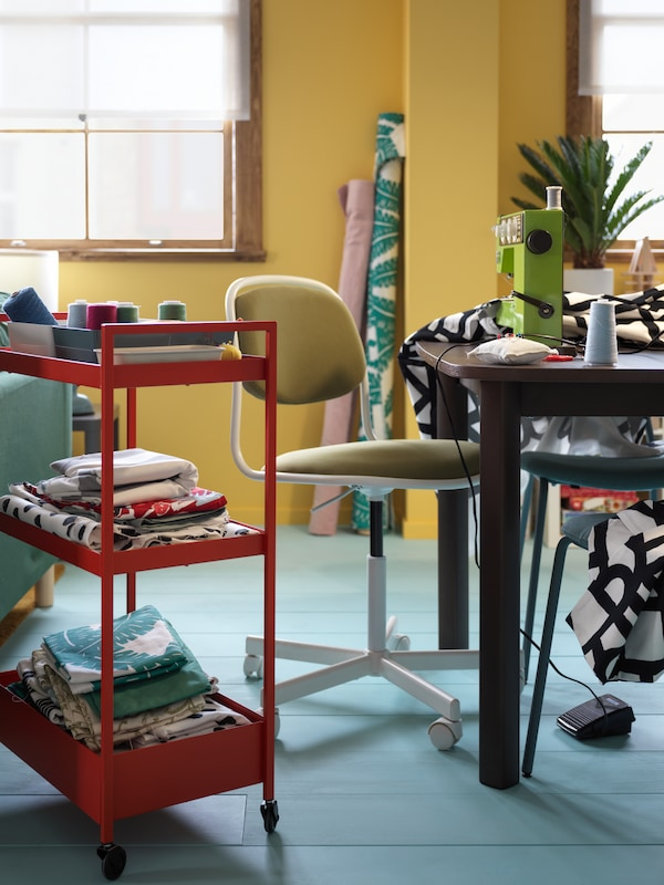 A white and yellow-green ÖRFJÄLL swivel chair in-between a table and a red NISSAFORS trolley filled with assorted fabric.