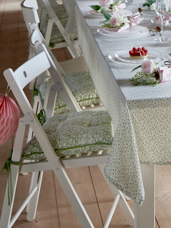 A white TERJE folding chair with an INBJUDEN chair cushion on it stands beside a table with an INBJUDEN tablecloth.