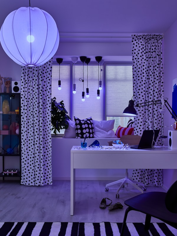 TRÅDFRI LED smart light bulbs in the ceiling lamp, window lamps and desk lamp change the colour of a workspace to blue.