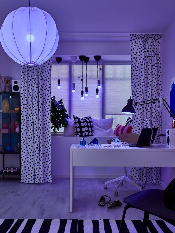 TRÅDFRI LED-Leuchtmittel in Decken-, Fenster- und Schreibtischleuchte ändern die Lichtfarbe in einem Arbeitsbereich in Blau.