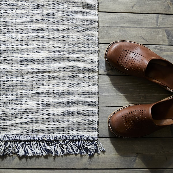 A pair of brown shoes sit on a wooden floor beside a TAULOV flatwoven rug which is made of cotton and jute.