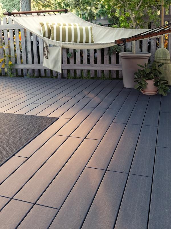Bodenbelag in Holzoptik auf einer Terrasse, u. a. mit einer beigen Hängematte mit zwei gestreiften Kissen, Topfpflanzen und einem Besen.
