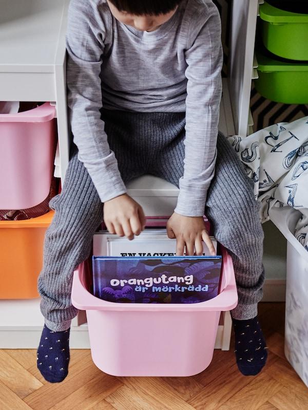 Assis sur un rangement TROFAST blanc, un jeune enfant saisit un livre dans une boîte TROFAST rose pâle.