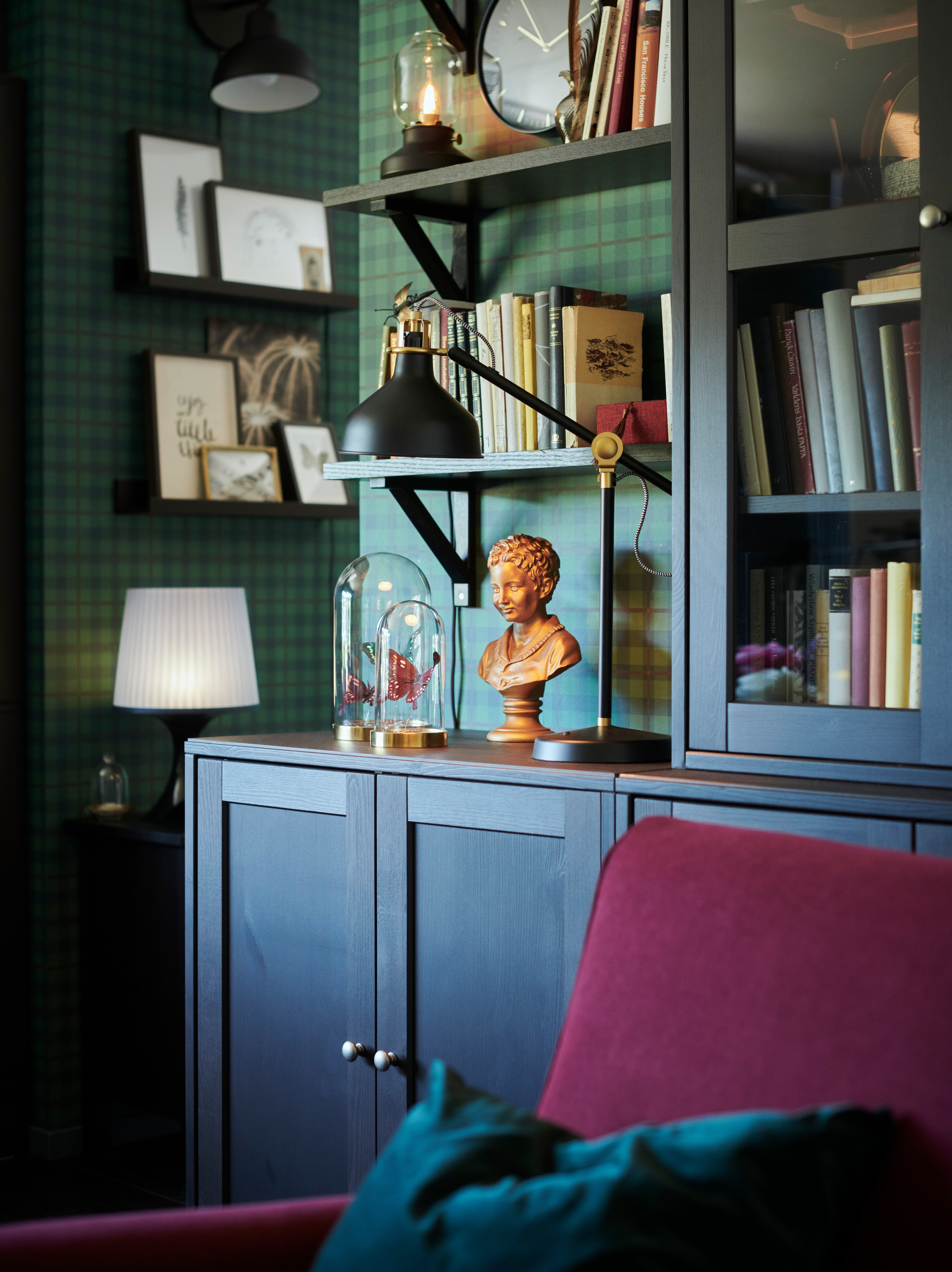 A black RANARP work lamp with an adjustable head and arm is on a cabinet, by an armchair and some shelves holding books.