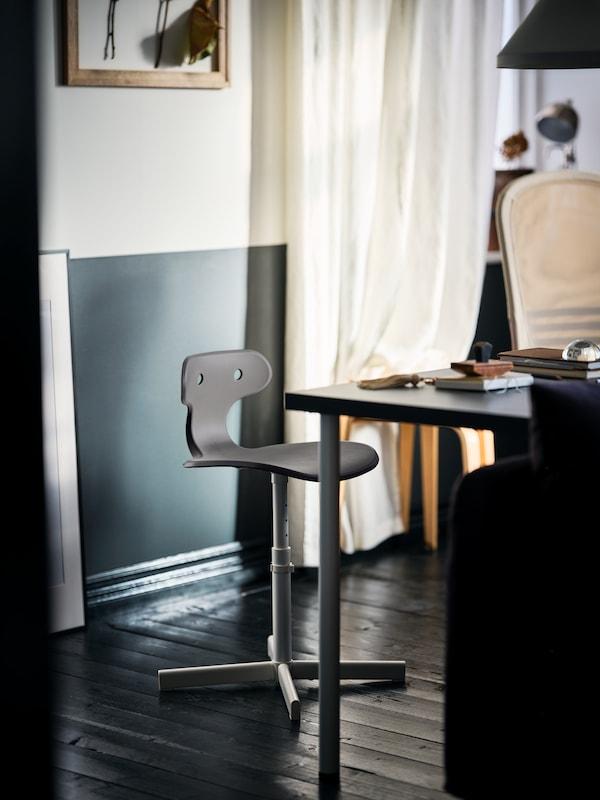MOLTE Drehstuhl steht an einem Tisch der aus einer LAGKAPTEN Tischplatte und ADILS Beinen besteht.