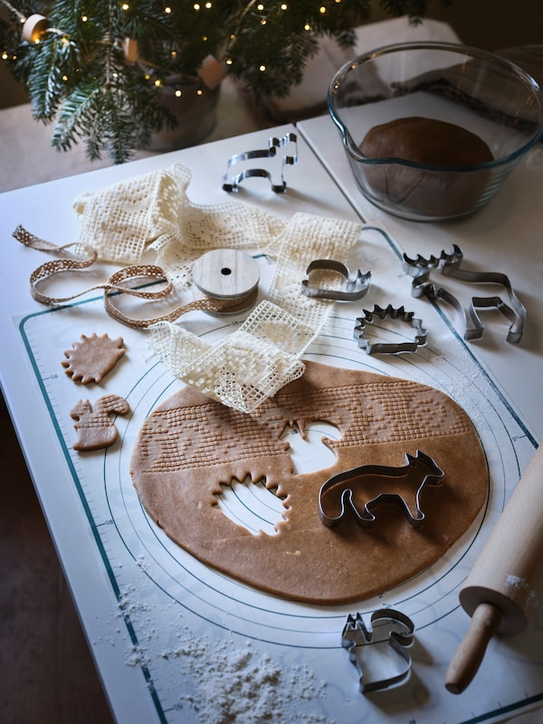 VINTERSAGA gingerbread dough rolled out on a table, with VINTER 2020 pastry cutters used to cut animal shapes in it.