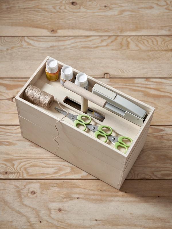 Närbild på en pyssellåda i plywood fylld med saxar, små färgburkar och tråd bland annat.