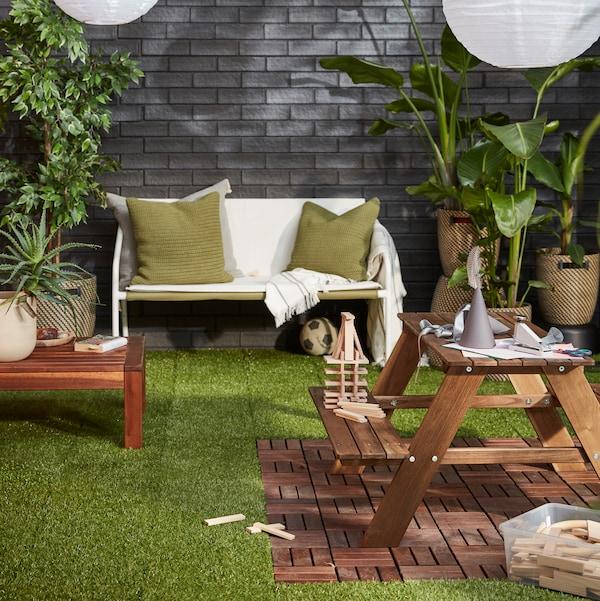 Gezellig terras bekleed met enkele leuke planten, met een INGMARSÖ 2-zitsbank bekleedt met kussens