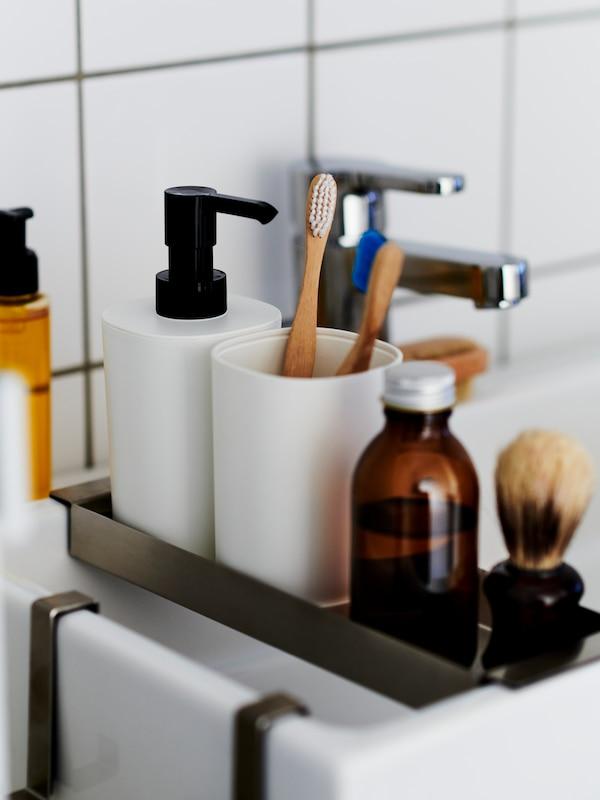 Primeiro plano dun dispensador de xabón STORAVAN en branco, un soporte para o cepillo de dentes e accesorios de afeitado nunha bandexa metálica sobre un lavabo.