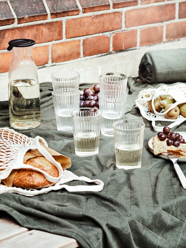 A picnic including drinks in VARDAGEN glasses and bread in KUNGSFORS net bags on an ODDHILD blanket by a brick wall.