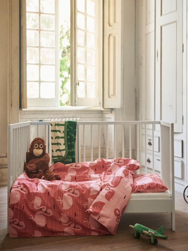 SUNDVIK 순드비크 기저귀교환대가 있고 벽에는 UPPLYST 우플뤼스트 LED 벽등 두 개가 달려 있으며 그 위에 아기 옷이 걸려 있는 침실.