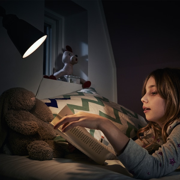Girl reading a book in her bed together with her teddy bear in the lamplight of an LED bulb.
