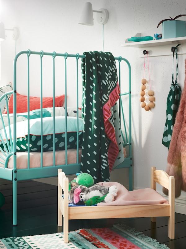 Pat de păpuși DUKTIG din lemn masiv de pin, cu lenjerie și jucării de pluș, lângă un pat turcoaz pentru copii.