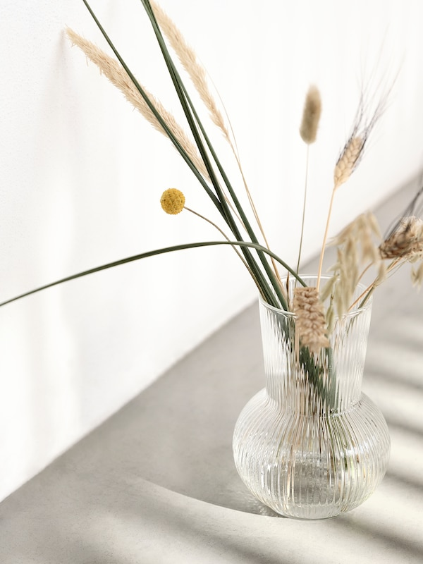 A clear glass PÅDRAG vase with cut plants in it sits on a floor near a wall. The floor has a striped shadow pattern on it.