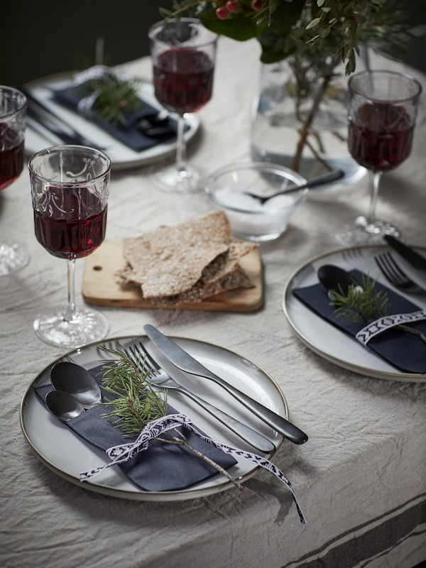 Decorative packages of MOTTAGA napkins and TILLAGD cutlery on grey GLADELIG plates on a subtly crinkled linen tablecloth.