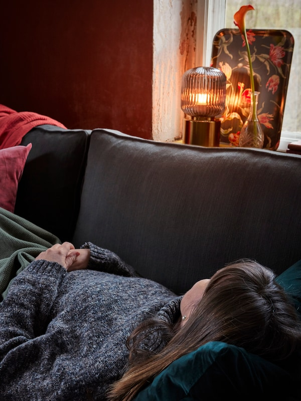 In a cozy living room, a woman takes a nap on a sofa. A table lamp set in the window provides warm light.
