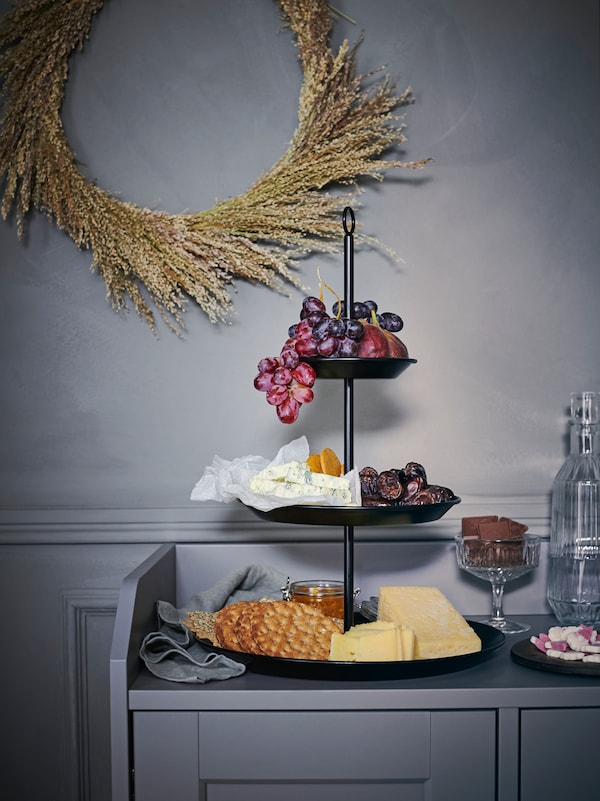 A black INBRINGANDE serving stand filled with fruits, cheeses, crackers and more, placed on a grey HAUGA sideboard.