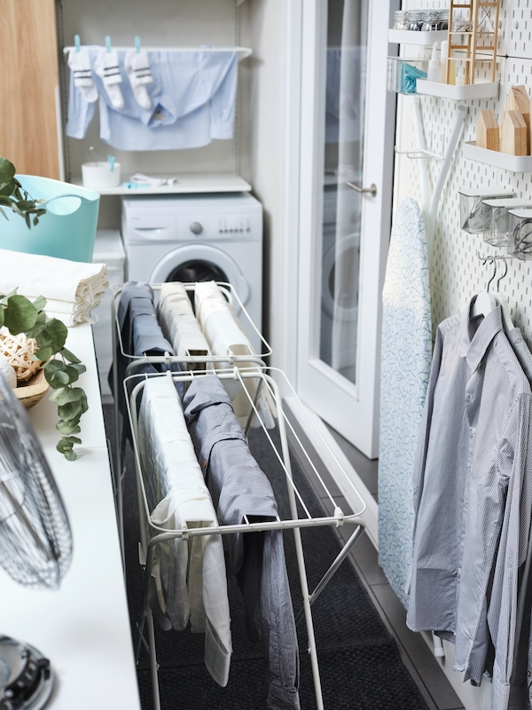 Two white JÄLL drying racks with clothes, beside white shelving and wall storage with shirts on hangers and an ironing board.