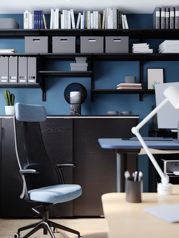 An office with closed storage and shelves holding boxes, files and diverse items, work desks with lamp and a chair.
