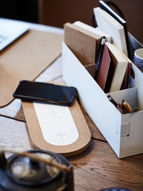 Mobiltelefon látható egy NORDMÄRKE hármas vezeték nélküli töltőegységre helyezve, egy KVISSLE íróasztali rendszerező mellett.