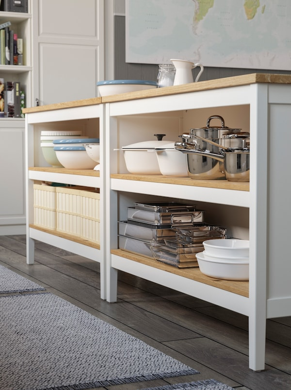 Two kitchen islands in a mix of off-white and oak storing cookware on open shelves.