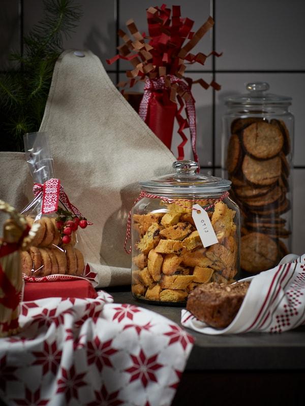 Un tarro de VARDAGEN relleno de galletas, rodeado por una barra de pan envuelta en un paño de cocina VINTER 2021 y otros productos horneados.