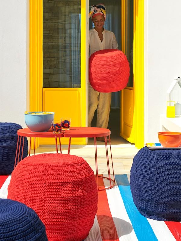 Zomerse kleurrijke rode en blauwe poefs voor buiten met een rood bijzettafeltje